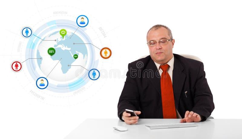 Geschäftsmann, der am Schreibtisch sitzt und ein Mobiltelefon mit Kugel hält stockfotografie