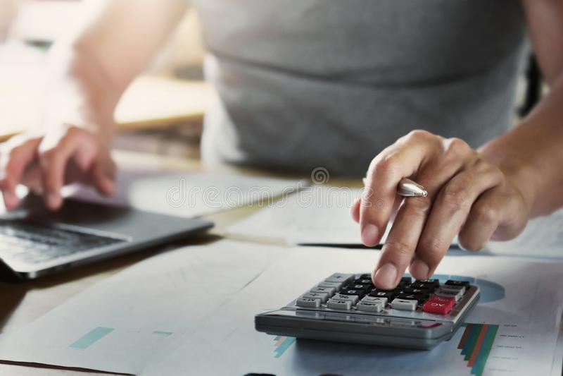 Geschäftsmann, der an Schreibtisch unter Verwendung des Taschenrechners arbeitet, um Daten der Finanzierung zu berechnen lizenzfreie stockfotografie