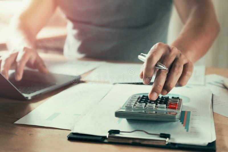 Geschäftsmann, der an Schreibtisch unter Verwendung des Taschenrechners arbeitet, um Daten der Finanzierung zu berechnen stockbild