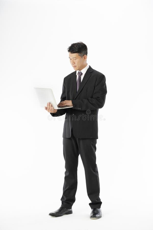 Geschäftsmann in der schwarzen Anzugsstellung und im halten Laptop lizenzfreie stockfotografie
