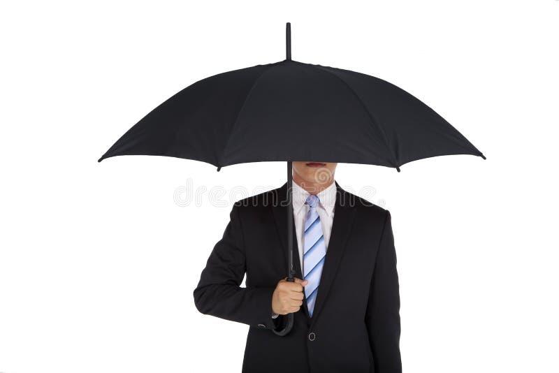 Geschäftsmann, der schwarzen Regenschirm anhält stockfoto