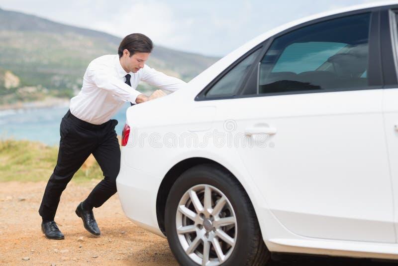 Geschäftsmann, der sein Auto drückt lizenzfreies stockfoto