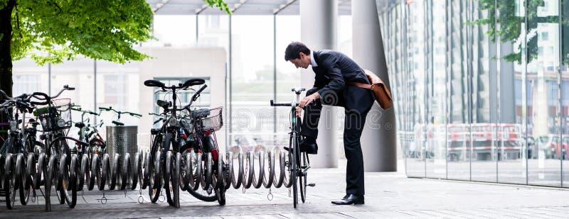 Geschäftsmann, der sein Fahrrad in der Stadt parkt stockfotografie