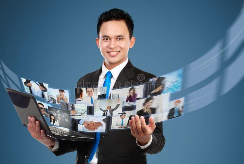 Geschäftsmann, der sein Foto und Videodateien unter Verwendung des Laptops teilt lizenzfreie stockfotos