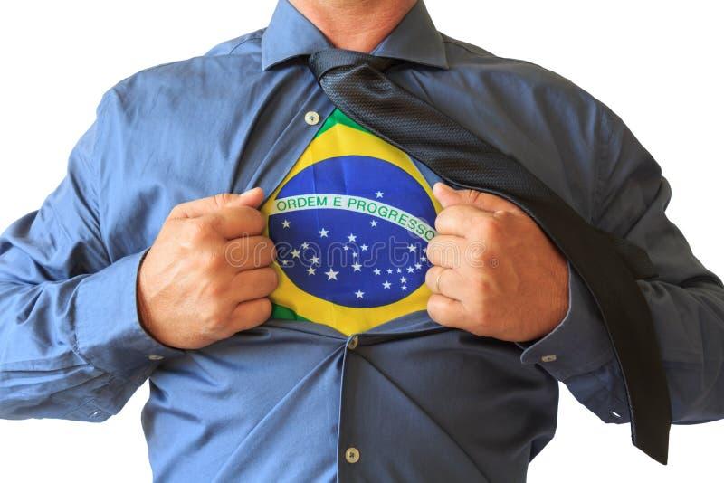 Geschäftsmann, der sein T-Shirt offen, Brasilien-Staatsflagge zeigend zieht Weißer Hintergrund lizenzfreie stockbilder