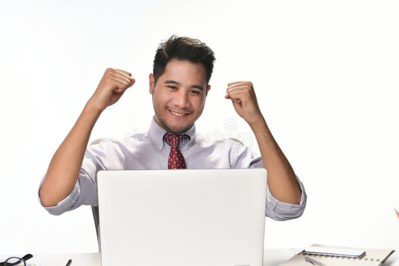 Geschäftsmann, der seine Hand sich fühlt glücklich für das Erzielen der Arbeit bei der Anwendung der Laptop-Computers anhebt lizenzfreies stockbild