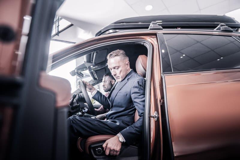 Geschäftsmann, der seine Rückenlehne beim Sitzen im Neuwagen drückt lizenzfreie stockfotografie