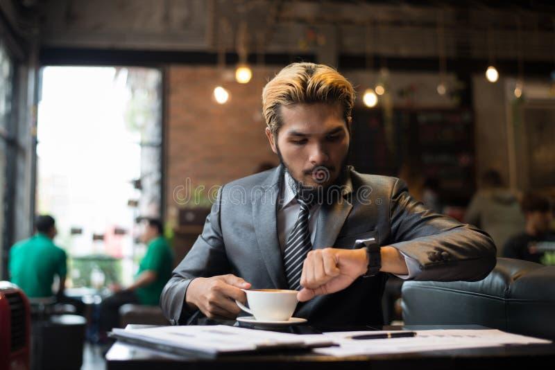 Geschäftsmann, der seine Uhr beim Arbeiten am Café betrachtet stockbilder
