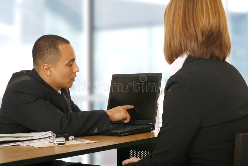 Geschäftsmann, der seinem Partner Laptop zeigt lizenzfreie stockbilder