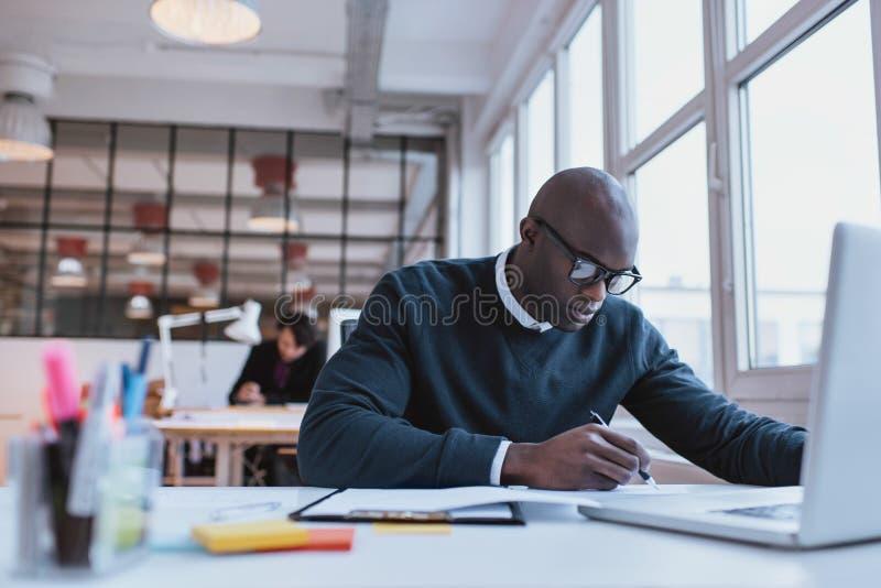 Geschäftsmann, der an seinem Schreibtisch arbeitet lizenzfreie stockfotografie