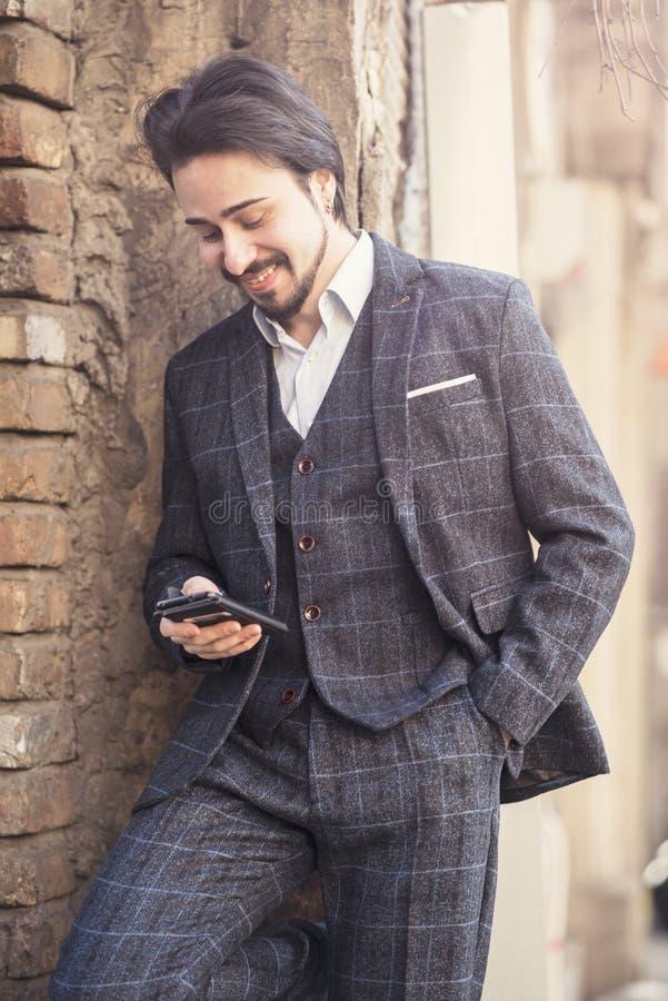 Geschäftsmann, der an seinem Telefon, englische Art spricht stockbilder
