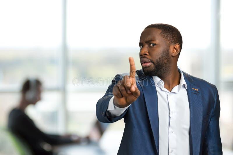 Geschäftsmann, der seinen Finger in Richtung zur Kamera zeigt stockfotografie