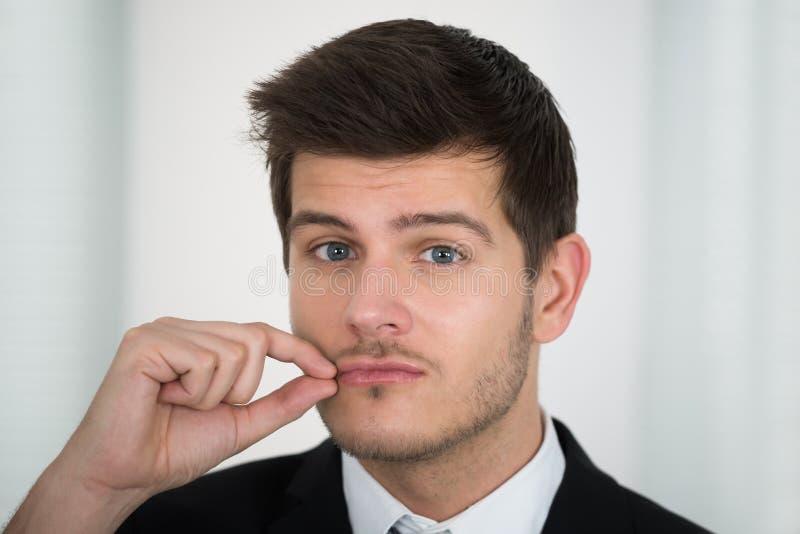 Geschäftsmann, der seinen Mund auf Reißverschluss schließt stockfotos