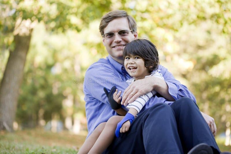 Geschäftsmann, der seinen Sohn auf Gras anhält lizenzfreie stockbilder