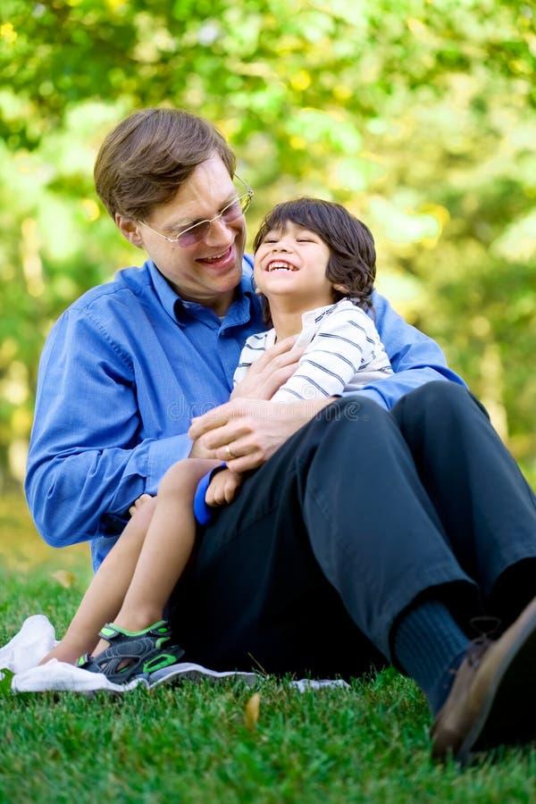 Geschäftsmann, der seinen Sohn auf Gras hält lizenzfreie stockfotos
