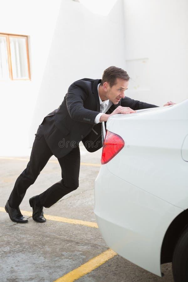 Geschäftsmann, der seins aufgegliedertes Auto drückt lizenzfreie stockfotos