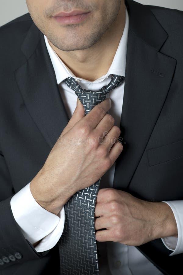 Geschäftsmann, der seins Gleichheit justiert lizenzfreie stockfotos