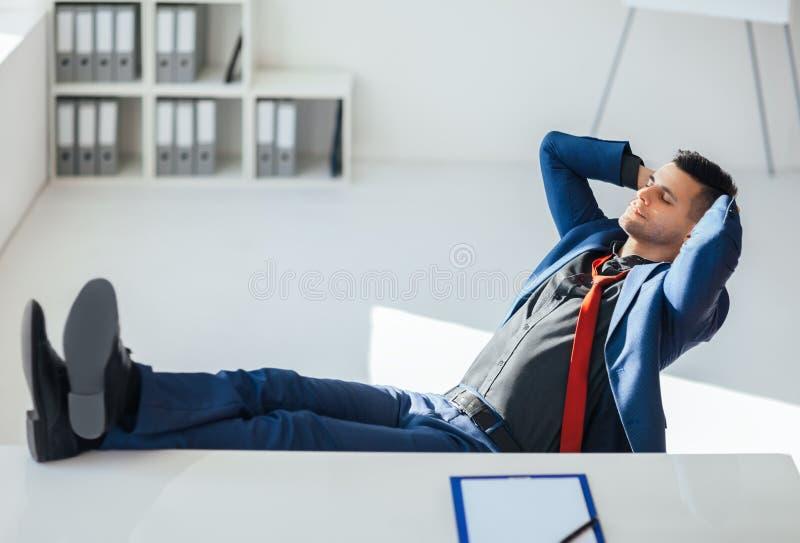 Geschäftsmann, der sich auf dem Tisch im Büro mit den Beinen entspannt stockfotos