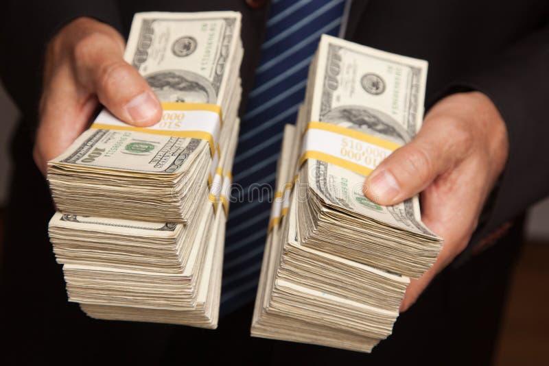 Geschäftsmann, der Stapel Geld überreicht stockfotografie