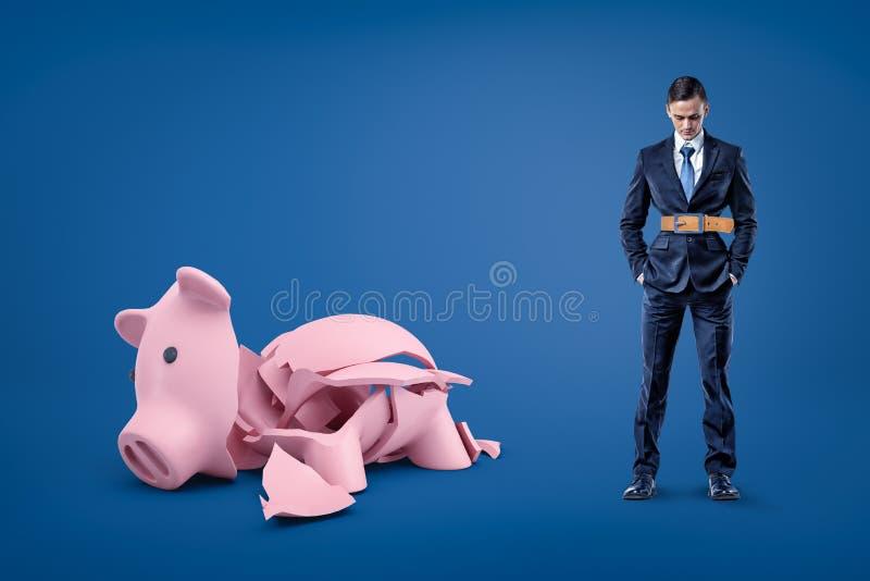 Geschäftsmann, der strammen Gurt und defektes Sparschwein auf blauem Hintergrund trägt stockbild