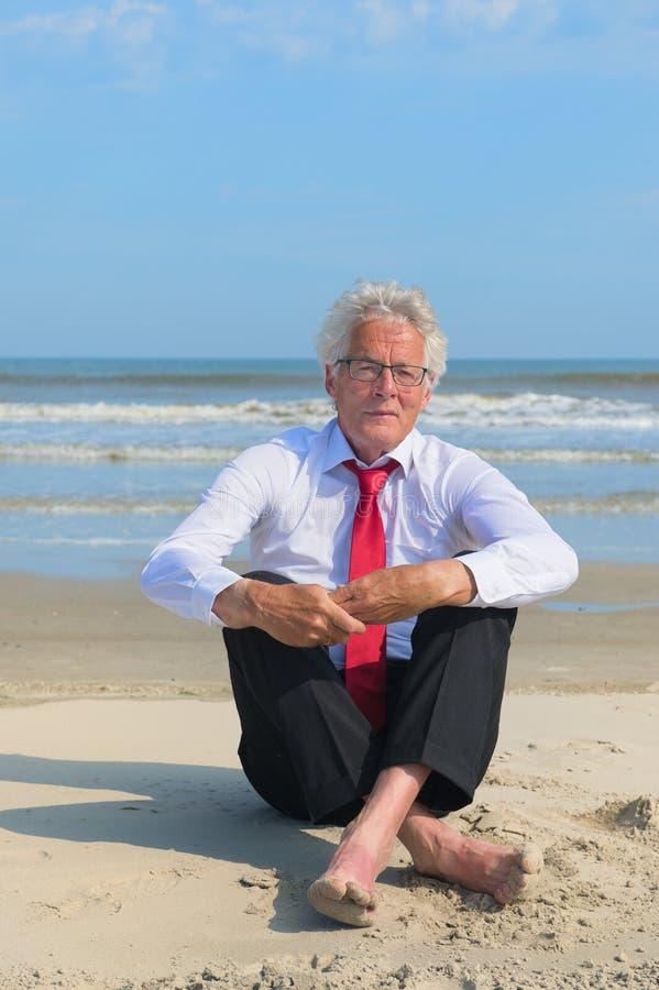 Geschäftsmann, der am Strand sitzt lizenzfreies stockbild