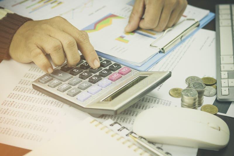 Geschäftsmann, der Taschenrechner für das Erklären und Finanzierung auf Arbeitstabelle am Morgen bedrängt lizenzfreie stockbilder