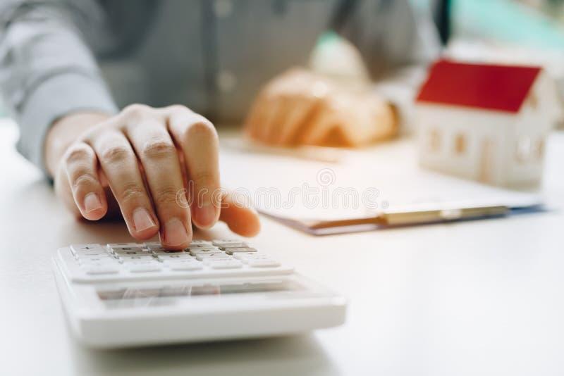 Geschäftsmann, der Taschenrechner verwendet, Budget über Hausvertragshypothek zu berechnen im Büroraum stockfotos