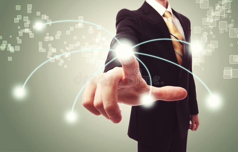 Geschäftsmann, der Technologieknopf bedrängt stockfoto