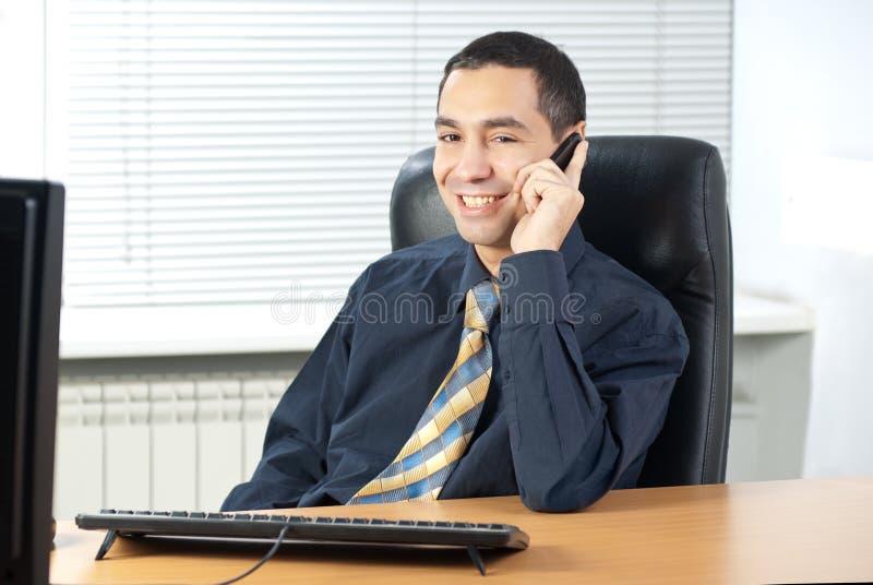 Geschäftsmann, der am Telefon im Büro spricht lizenzfreie stockfotografie