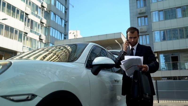 Geschäftsmann, der am Telefon nahe dem Auto, Finanzfragen der Firma lösend spricht lizenzfreie stockbilder
