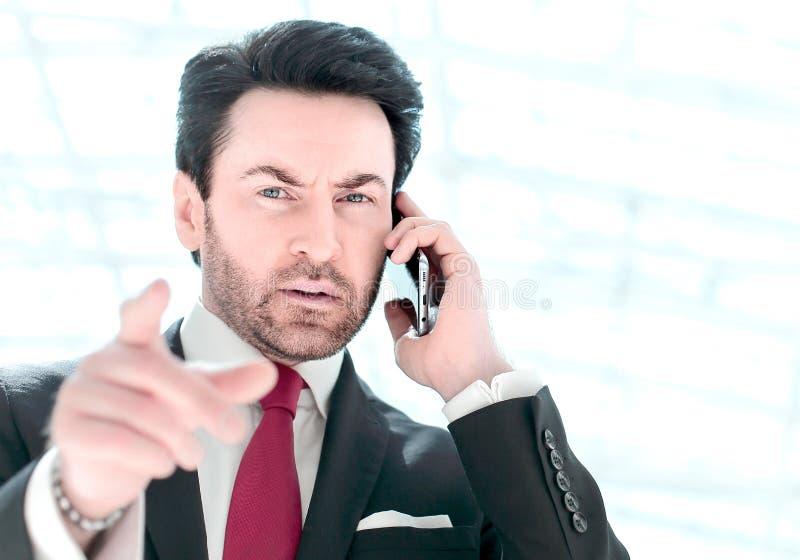 Geschäftsmann, der am Telefon spricht und auf Sie zeigt lizenzfreie stockfotografie