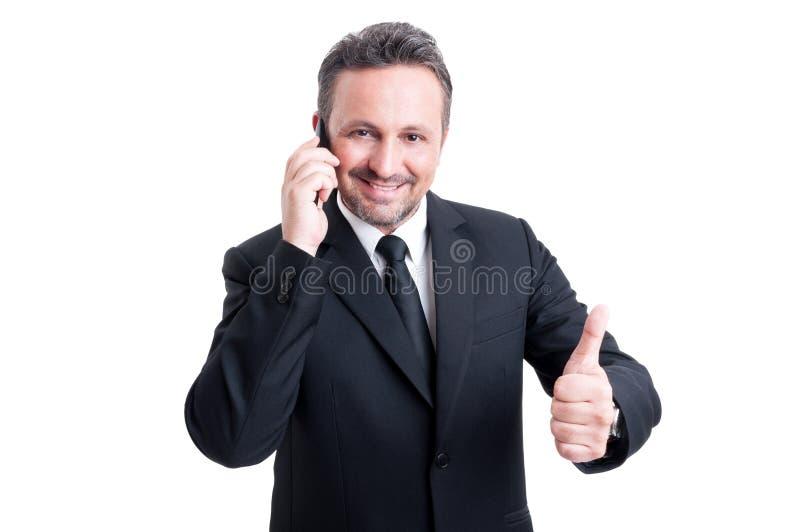 Geschäftsmann, der am Telefon spricht und sich Daumen zeigt lizenzfreies stockfoto