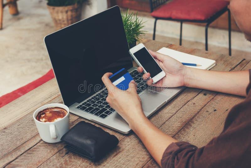 Geschäftsmann, der Telefon und Zahlungskreditkarte mit Laptop O hält lizenzfreie stockbilder