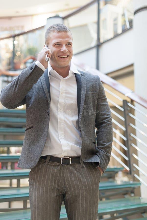Geschäftsmann, der über smartphone im Geschäftsgebäude spricht lizenzfreie stockbilder