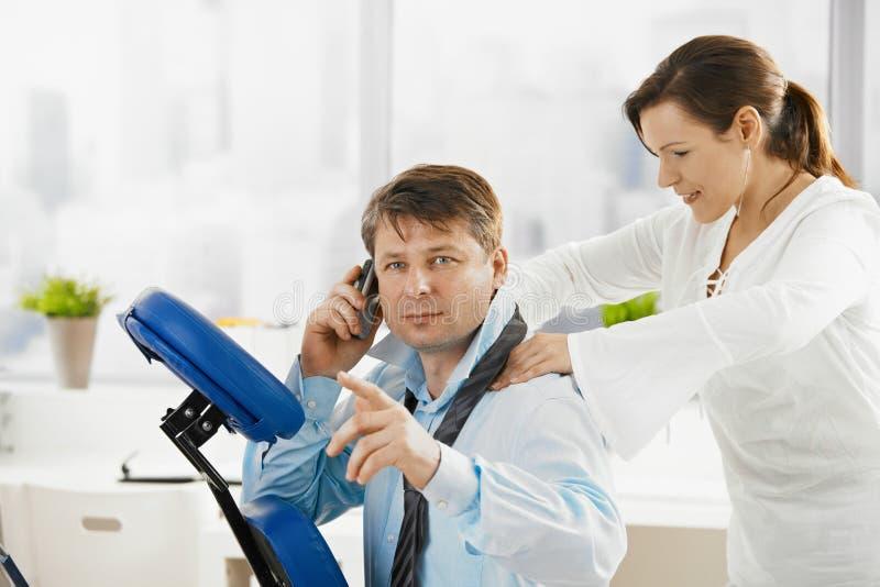 Geschäftsmann, der am Telefon während der Massage spricht lizenzfreies stockbild