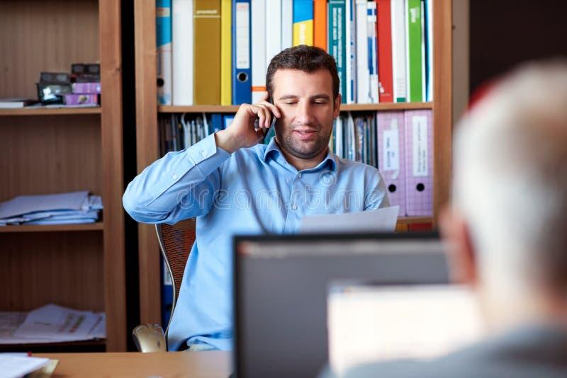 Geschäftsmann, der telefonisch Schreibarbeit in einem Büro bespricht stockfoto
