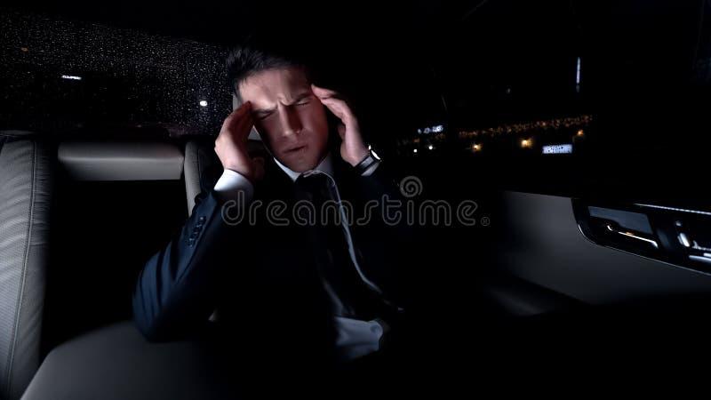 Geschäftsmann, der Tempel im Auto auf Heimweg, starke Kopfschmerzen, stressiger Job massiert lizenzfreie stockfotos