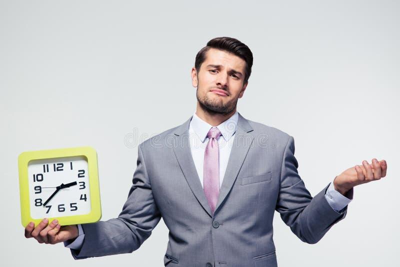 Geschäftsmann, der Uhr und copyspace hält lizenzfreies stockfoto