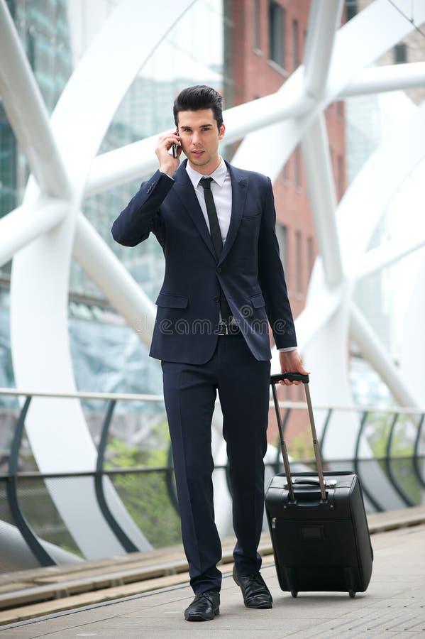 Geschäftsmann, der um Telefon ersucht und mit Tasche an der Metrostation reist lizenzfreie stockfotografie