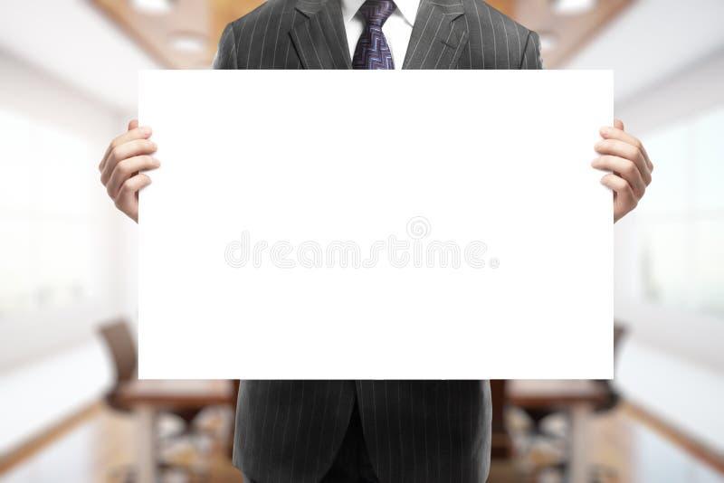 Geschäftsmann, der unbelegtes Plakat anhält lizenzfreies stockfoto