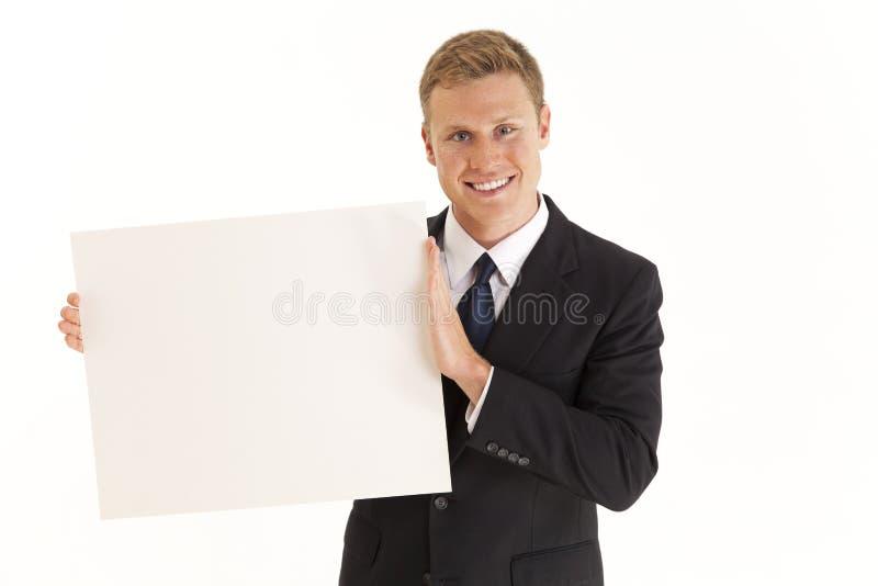 Geschäftsmann, der unbelegtes Plakat hält stockbilder