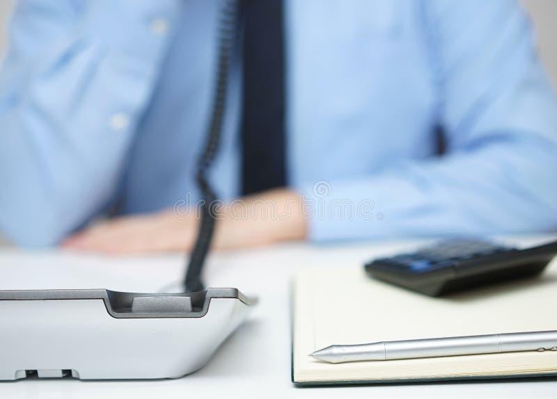 Geschäftsmann in der Unschärfe sprechend auf dem Telefon, Fokus auf Stift und telep lizenzfreie stockfotos
