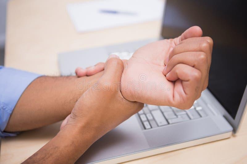 Geschäftsmann, der unter den Handgelenkschmerz leidet lizenzfreie stockbilder
