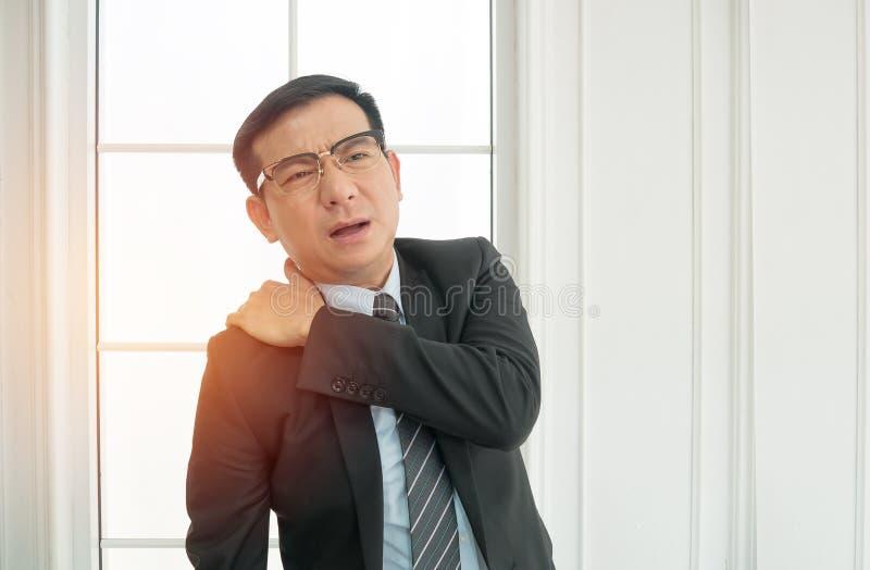 Geschäftsmann, der unter den Schulterschmerz im Büro leidet stockbild