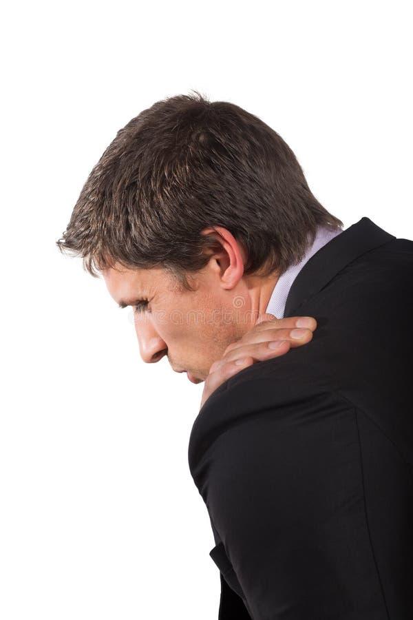 Geschäftsmann, der unter den Schulterschmerz leidet lizenzfreies stockfoto