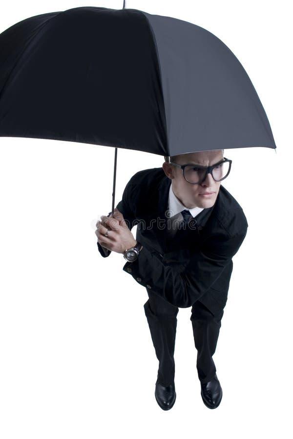 Geschäftsmann, der unter einem Regenschirm sich versteckt lizenzfreie stockfotos