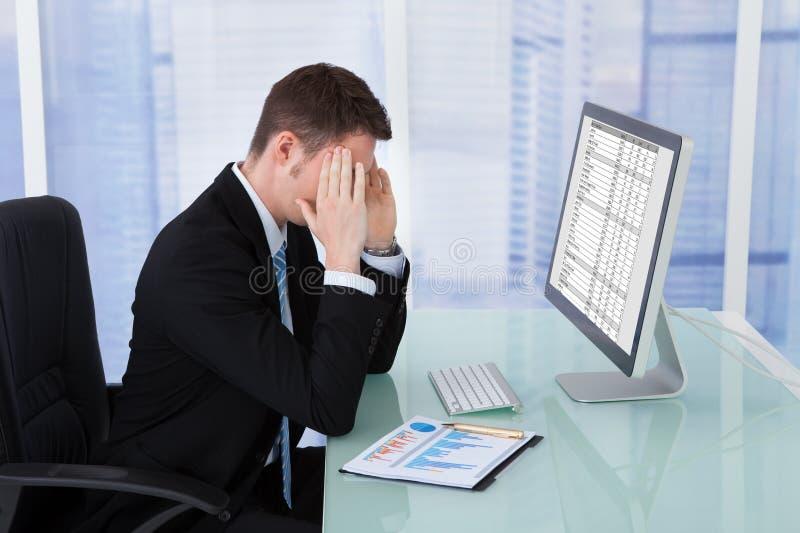 Geschäftsmann, der unter Kopfschmerzen am Computertisch leidet stockbild