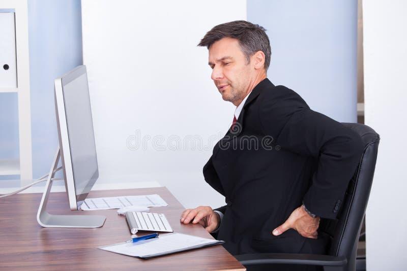Geschäftsmann, der unter Rückenschmerzen leidet stockfotografie