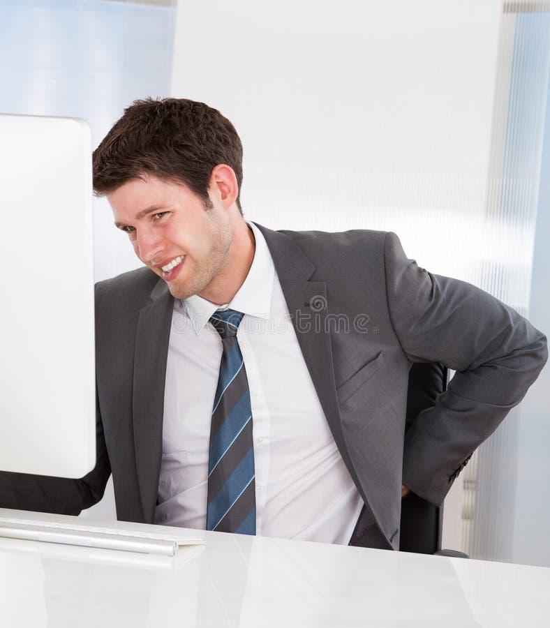 Geschäftsmann, der unter Rückenschmerzen leidet lizenzfreies stockbild
