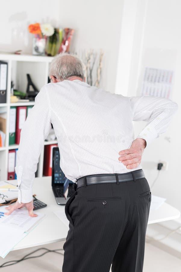 Geschäftsmann, der unter Rückenschmerzen leidet lizenzfreie stockfotografie
